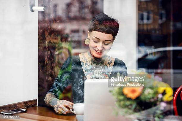 Young tattooed woman in a café.