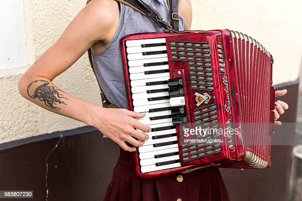 Young tattooed woman musician plays accordion in Montmartre, Paris