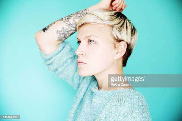 young tattooed woman on blue - rekha garton stock pictures, royalty-free photos & images