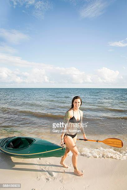 Young tattooed woman with kayak on beach.