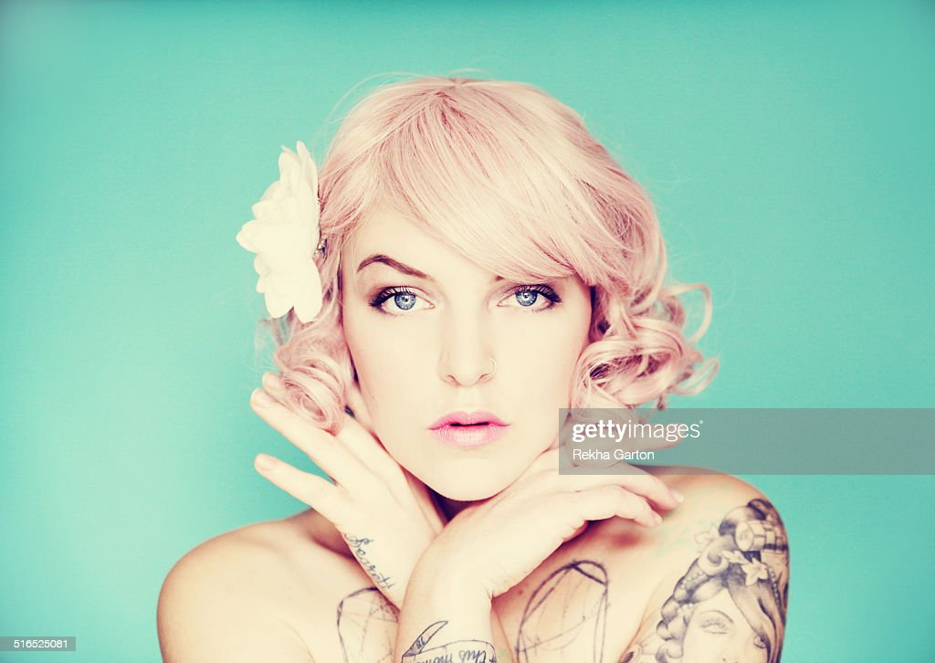 Young tattooed woman with pink hair and tattoos