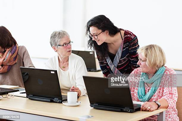 young teacher and senior adults learning in computer lab