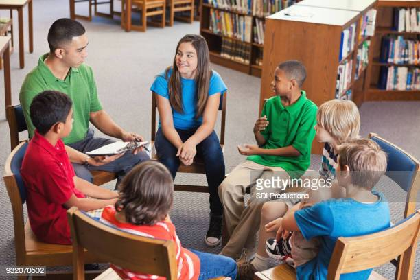 Young teacher leads after school club in library