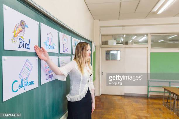 young teacher teaching english language in classroom - linguistics stock pictures, royalty-free photos & images