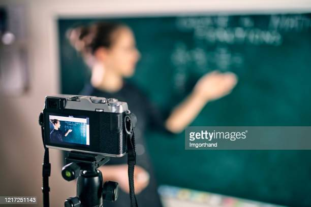 young teacher teaching remotely using camera to stream lesson - remote location stock pictures, royalty-free photos & images