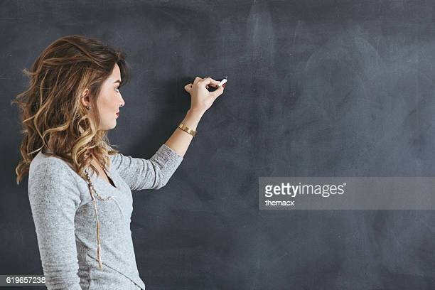Young teacher writing on a blackboard