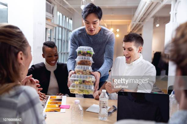 young team eating in the office at lunch break - lunch stock pictures, royalty-free photos & images