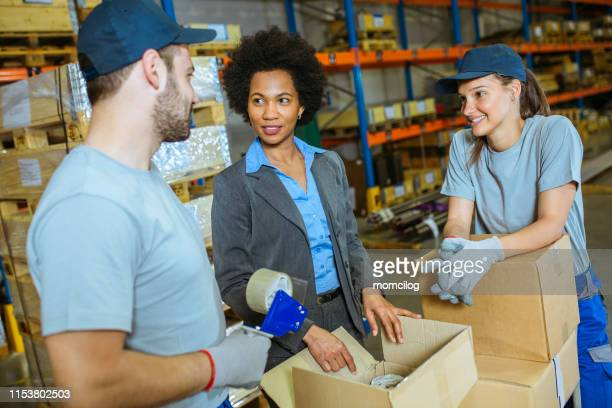 young team manual workers and supervisor standing inside warehouse with package - post office stock pictures, royalty-free photos & images