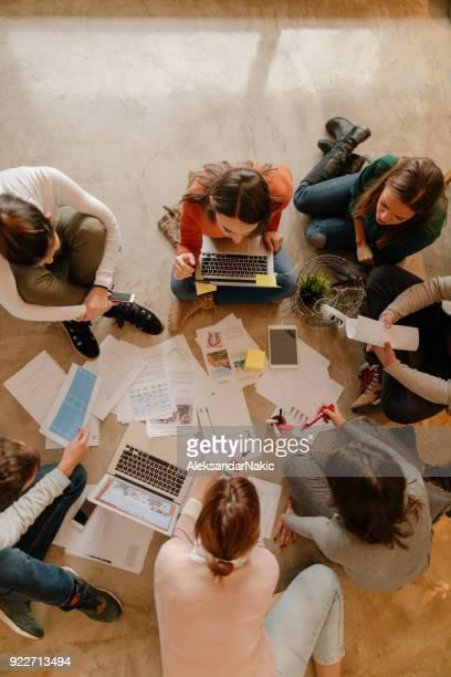 jeune équipe qui travaille sur leur métier de démarrage - groupe moyen de personnes photos et images de collection