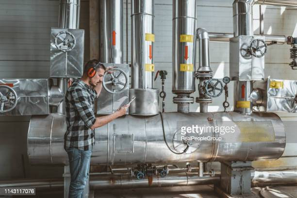 young technician is checking heating system in boiler room - boiler stock pictures, royalty-free photos & images