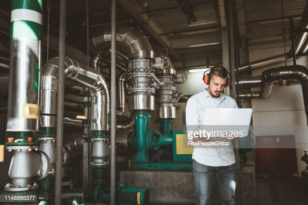 young technician is checking heating system in boiler room - district heating plant stock pictures, royalty-free photos & images