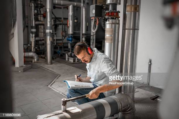 young technician is inspecting heating system in boiler room - district heating plant stock pictures, royalty-free photos & images
