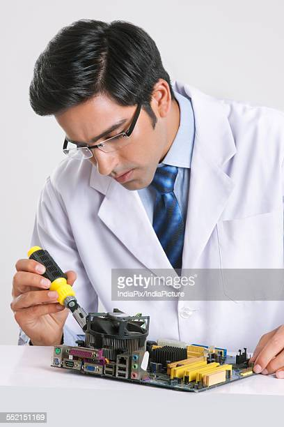 Young technician repairing machine part at table over gray background