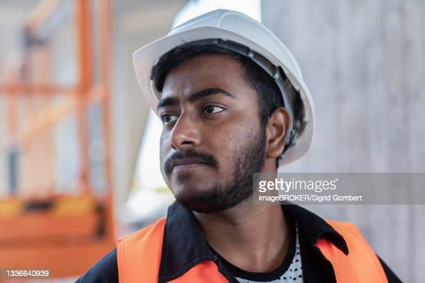 young technician with beard working outside with helmet, baden-wuerttemberg, germany - sigrid gombert stock pictures, royalty-free photos & images