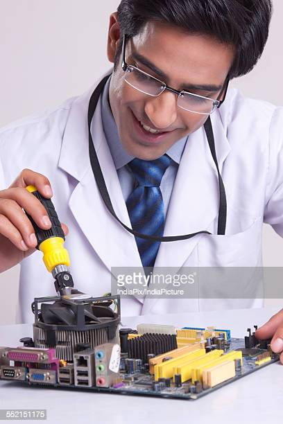 Young technician working on computer part against gray background