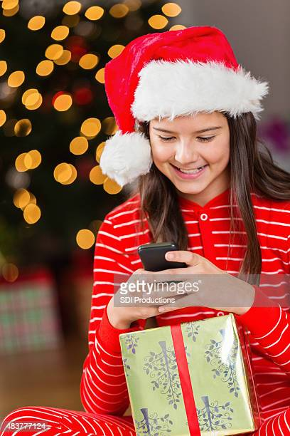 Young teen girl opens cell phone as Christmas gift
