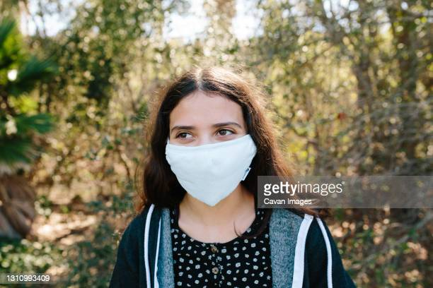young teen girl outside smiles under a face mask - thousand oaks stock pictures, royalty-free photos & images