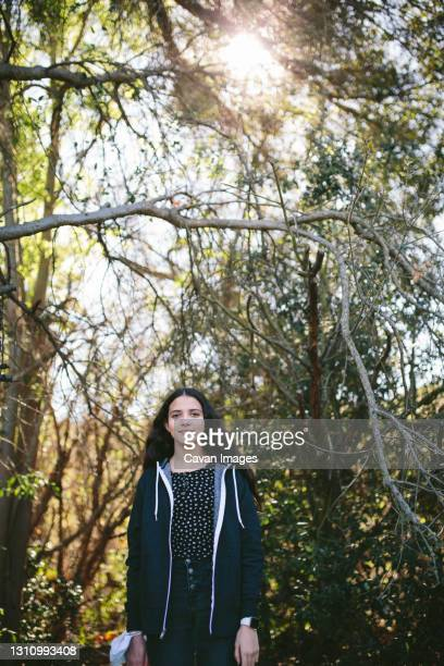a young teen girl outside with a face mask around her wrist - thousand oaks stock pictures, royalty-free photos & images