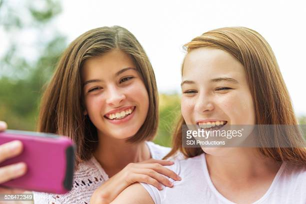 young teen girls taking selfie photo with cell phone camera - cute highschool girls stock photos and pictures