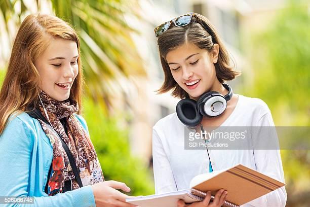 Jeune teen étudiants comparer les devoirs des notes à l'extérieur de l'école
