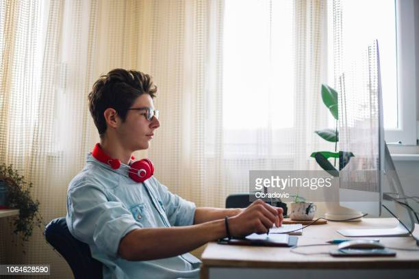 young teenage boy  - graphic designer at work - illustrator stock photos and pictures