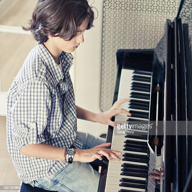 young teenage boy playing piano - keyboard player stock photos and pictures