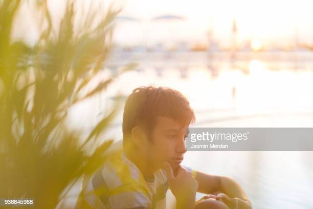 young teenage boy sitting outdoors - アフィントン ストックフォトと画像