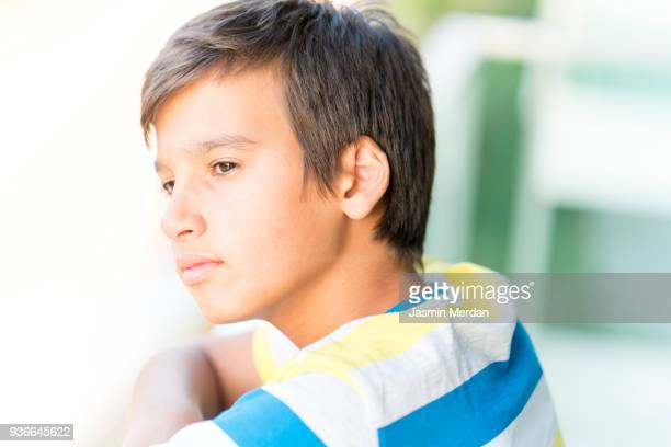 Young Teenage Boy Standing in Front of a Window