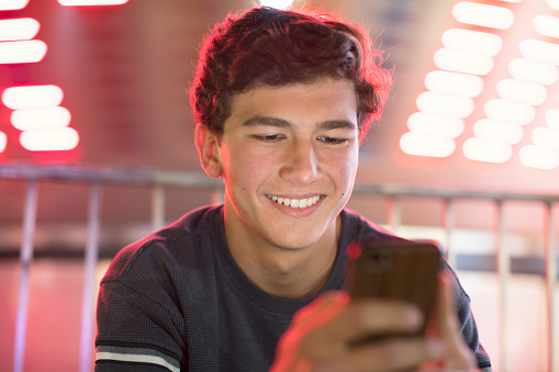 Young teenage boy texting at a fair at night - gettyimageskorea