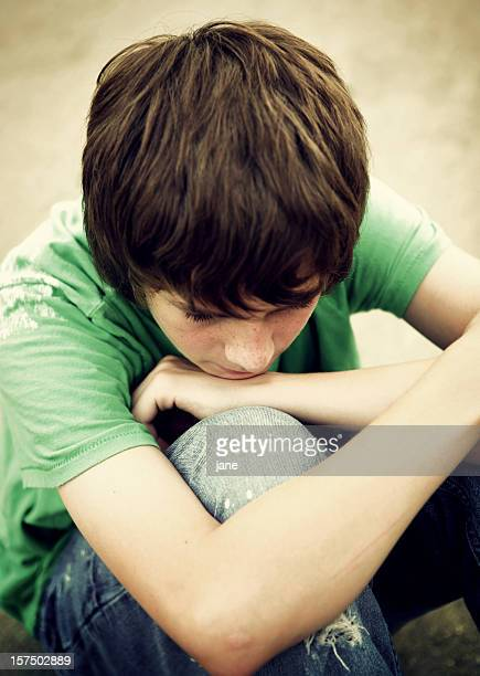 Young teenage boy with arms crossed and head on knees