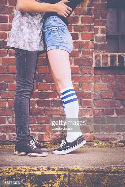 young teenage couple embracing and kissing - leg kissing stock photos and pictures