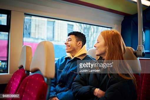 Young teenage couple on a bus laughing and enjoying a moment together