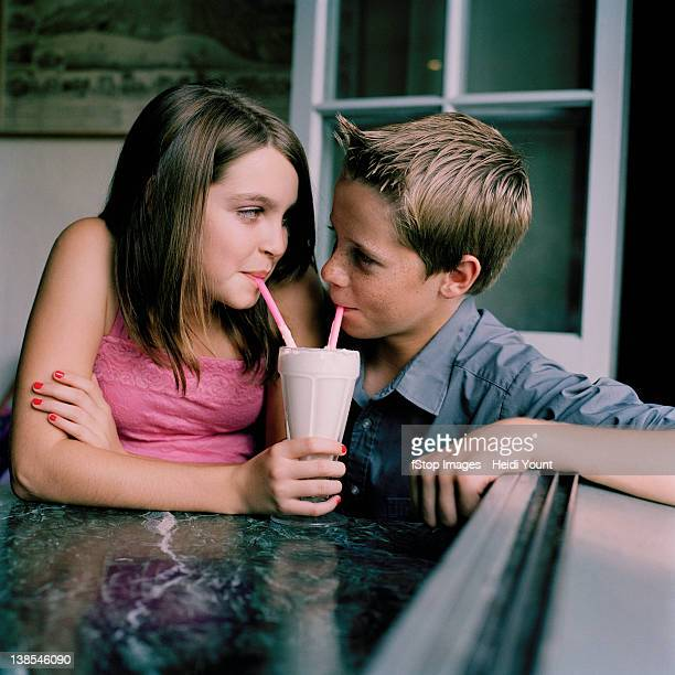 A young teenage couple sharing a milkshake at a diner