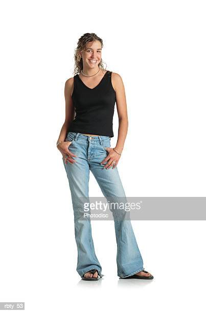 young teenage female with brown long curly permed hair pulled back halfway wearing a black tank top blue jeans and thongs looks into the camera and smiles - girl wear jeans and flip flops stock photos and pictures