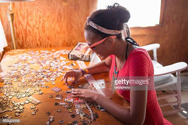 a young teenage girl doing a puzzle on summer vacation - heshphoto stockfoto's en -beelden