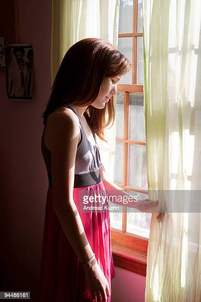 Young teenage girl looking out of window.