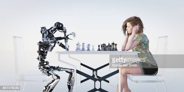 Young teenage girl plays chess with robot