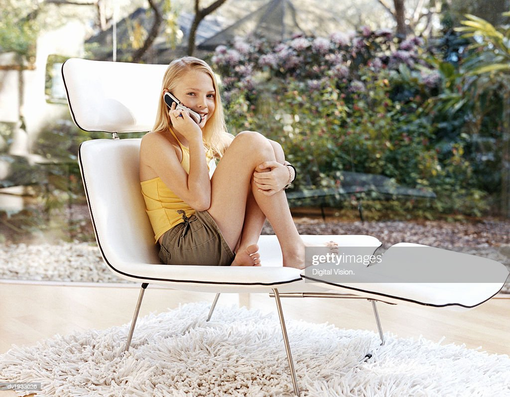 Young Teenage Girl Sitting on a Lounger Chair Using a Mobile Phone : Stock Photo