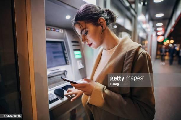 junge teenager-mädchen mit geldautomaten und smartphone - geldautomat stock-fotos und bilder