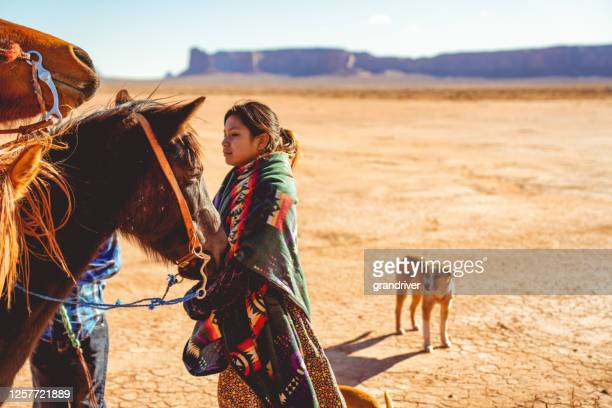 young teenage navajo girl on a horse in the beautiful desert of monument valley arizona - apache stock pictures, royalty-free photos & images