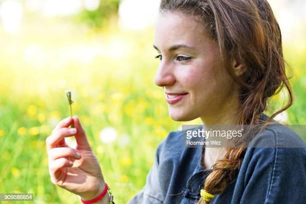 young teenage woman holding a blown dandelion - feuille de pissenlit photos et images de collection