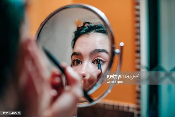 young teenager applying eyeliner in domestic bathroom - eyeliner stock pictures, royalty-free photos & images