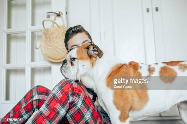 young teenager boy in pajama snuggling his english bulldog at home - 突き出た鼻 ストックフォトと画像