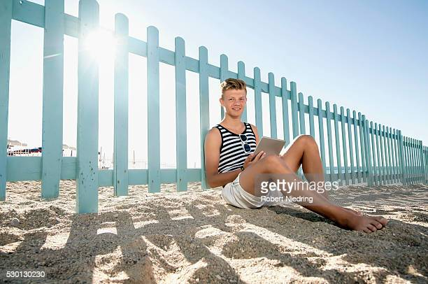 young teenager boy using tablet computer beach - handsome black boy stock photos and pictures
