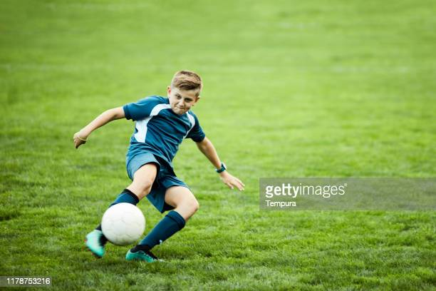 young teenager executes a perfect soccer volley. - shooting at goal stock pictures, royalty-free photos & images