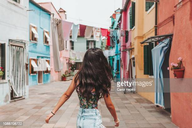 young teenager in casual clothes walking in Burano street,Italy