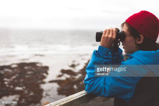 Young teenager looking at the sea with binoculars. Whales watching. Gaspesie, Quebec, Canada