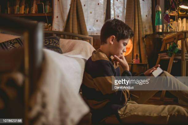 young teenager using his smartphone at home - pre adolescent child stock pictures, royalty-free photos & images