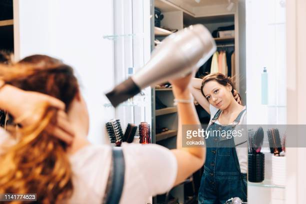 young teenager woman using hair dryer in front of mirror - blow drying hair stock pictures, royalty-free photos & images