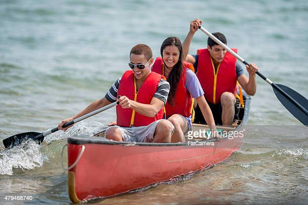 young teenagers on a canoe trip - paddling stock pictures, royalty-free photos & images